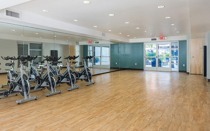 Fitness area with exercise bikes on wood floor at the Glendale apartments community The Howard