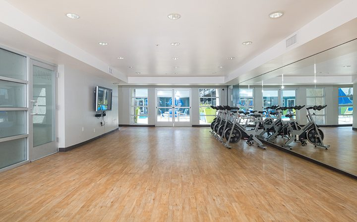 Exercise bikes in mirrored fitness area at The Howard, apartments in Glendale
