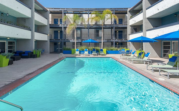 Resort-style pool with chairs and blue umbrellas at The Howard, apartments in Glendale