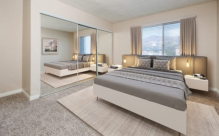 Furnished bedroom with carpeting in a model unit at The Howard, apartments in Glendale