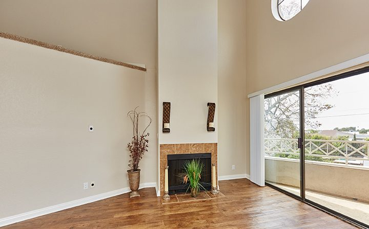 Furnished living room with fireplace and balcony at The Jeremy, apartments in West Los Angeles