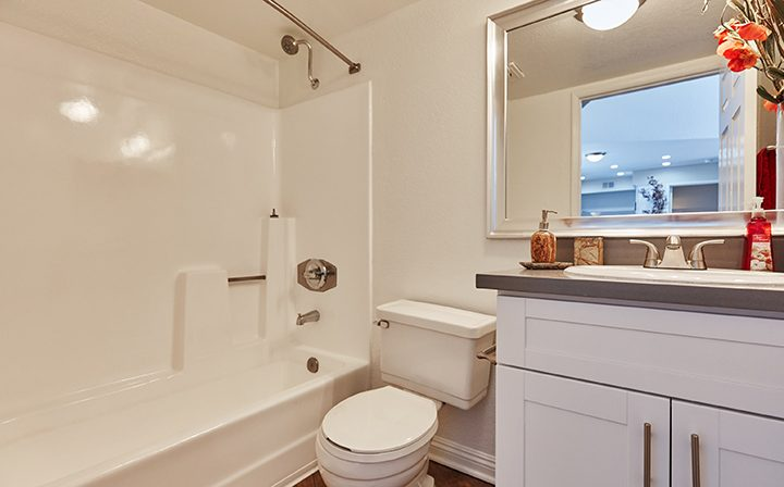 Furnished bathroom with white cabinets at The Jeremy, apartments in West Los Angeles