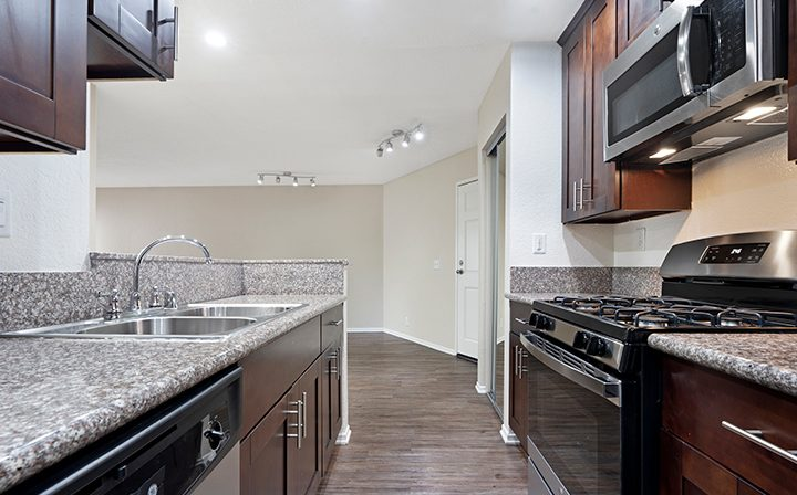Kitchen with sink opposite range and hardwood floors at The Jeremy, apartments in West Los Angeles