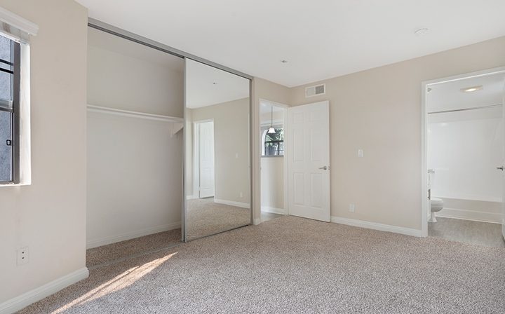 Carpeted unfurnished bedroom with mirrored closet at The Jeremy, apartments in West Los Angeles