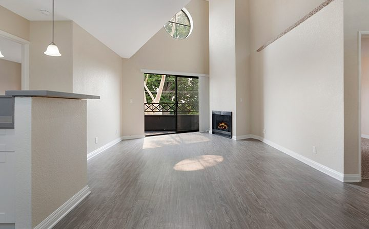 Unfurnished living room with tall ceiling and porthole at The Jeremy, apartments in West Los Angeles