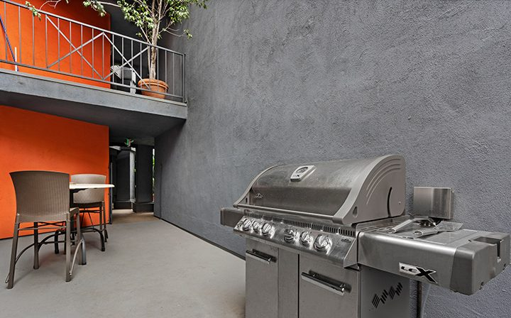 BBQ grill next to seating in the courtyard at the West Los Angeles apartments community The Jeremy