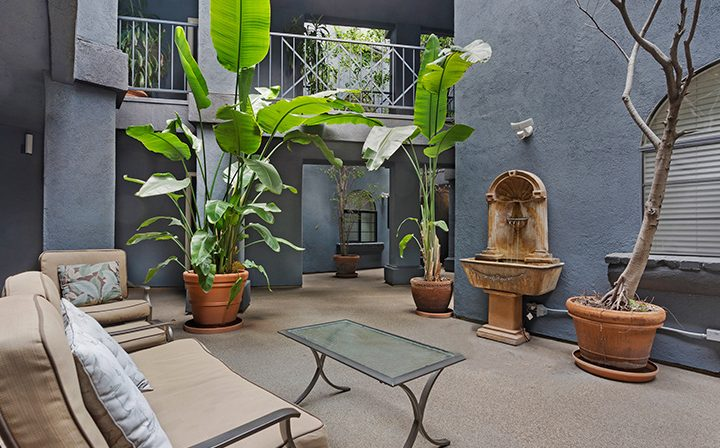 Elegant courtyard with fountain, plants, and seating at The Jeremy, apartments in West Los Angeles
