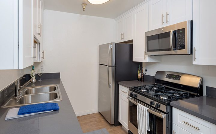 Kitchen with white walls and cabinets at the Hollywood apartments community The Jessica