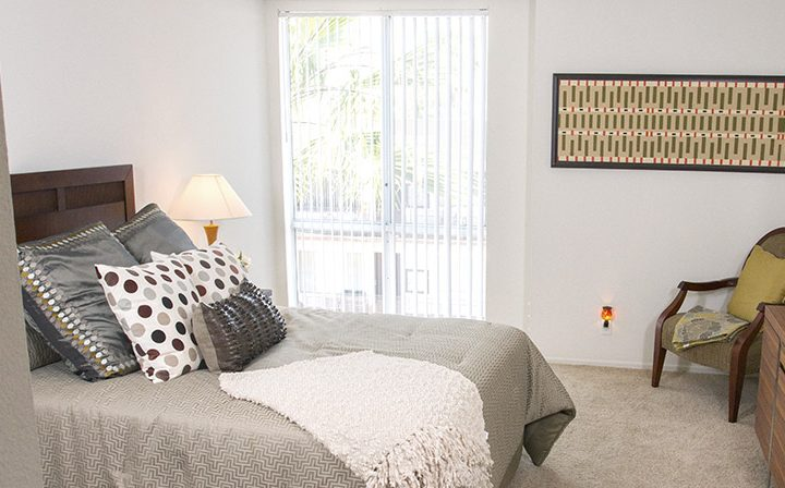 Furnished bedroom with carpeted floor and wall-high window at The Jessica, apartments in Hollywood