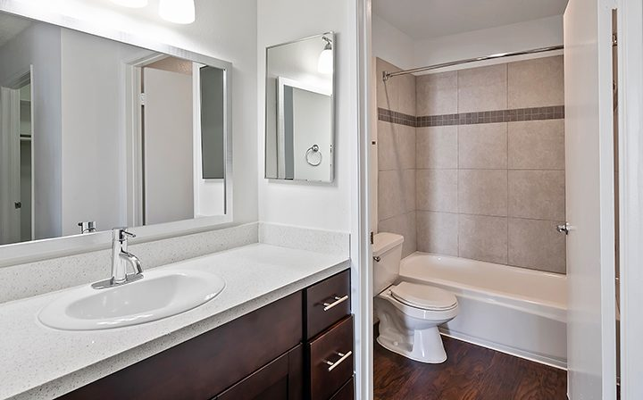 Unfurnished bathroom with brown cabinets and flooring at The Jessica, apartments in Hollywood