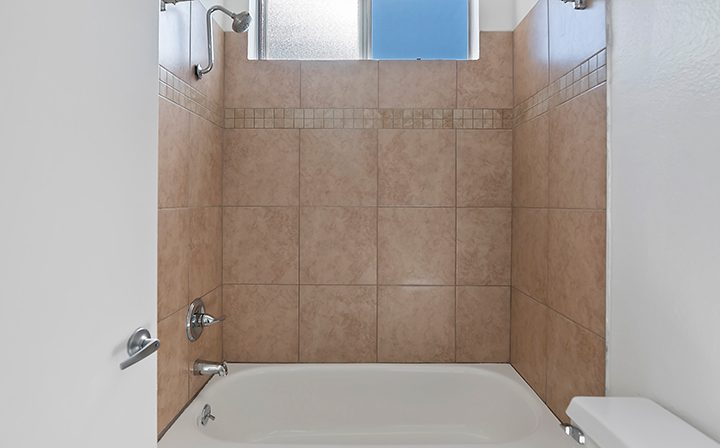 Shower/tub combo with brown tiled wall at Hollywood apartments community The Jessica