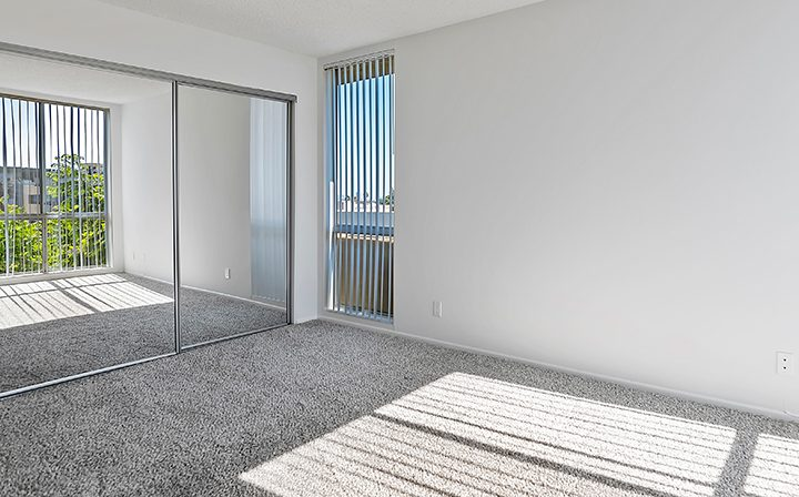 Unfurnished, carpeted bedroom with mirrored closet at The Jessica, apartments in Hollywood