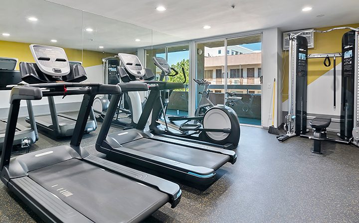 Exercise machines in mirrored fitness center at The Jessica, apartments in Hollywood