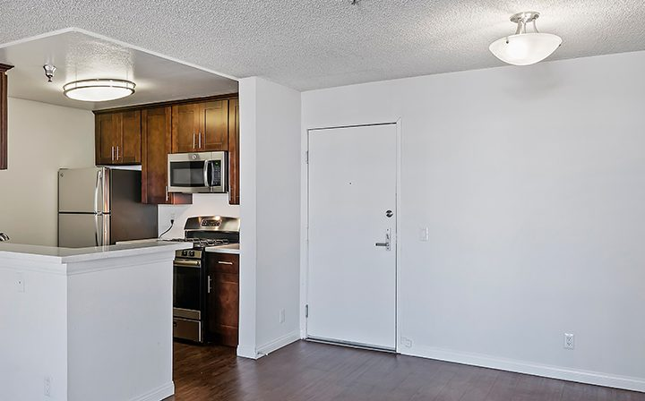 Unfurnished apartment with corner kitchen and brown cabinets at The Jessica, apartments in Hollywood