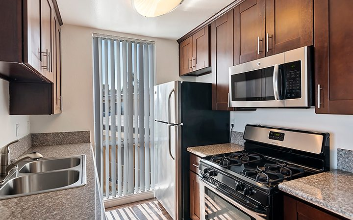 Unfurnished kitchen with brown cabinets and tall window at The Jessica, apartments in Hollywood