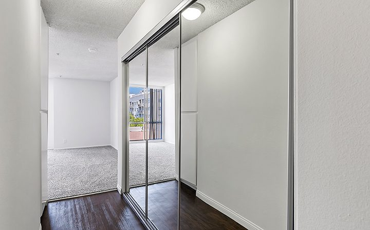 Hallway with mirrored closet leading to bedroom at Hollywood apartments community The Jessica