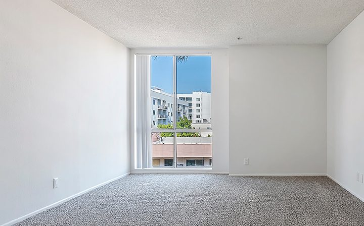 Carpeted, unfurnished bathroom with wall-high window at Hollywood apartments community The Jessica