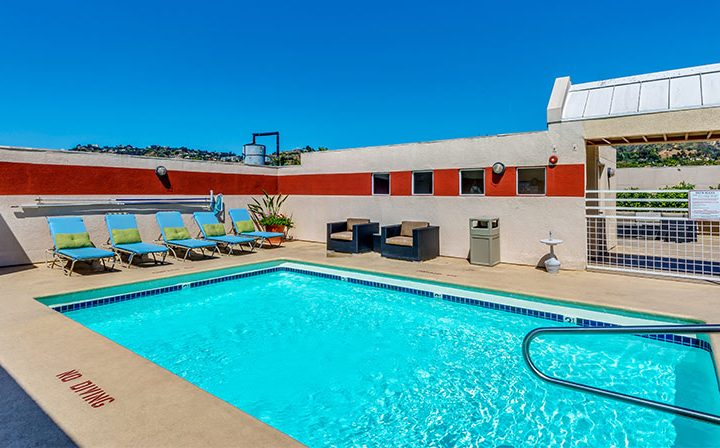 Rooftop pool with red wall accents on a clear, sunny day at The Joshua, apartments in Hollywood