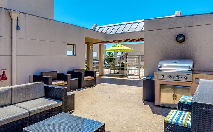 Outdoor BBQ and lounge area near pool at the Hollywood apartments community The Joshua