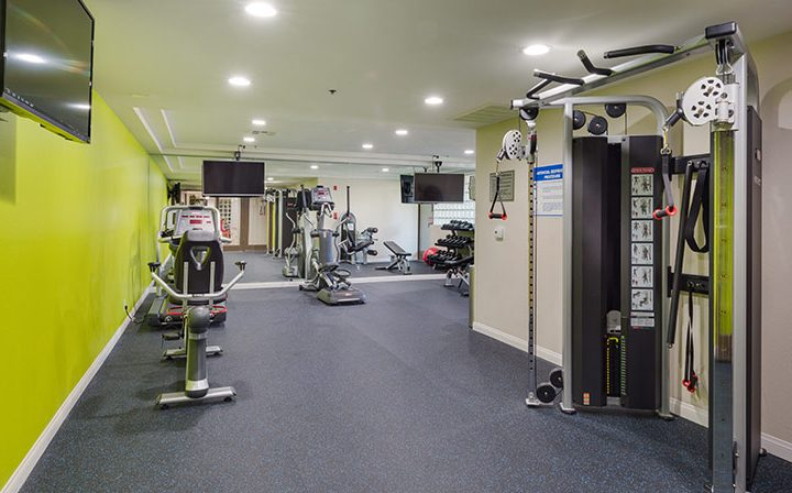 State-of-the-art fitness center with lime green wall at The Joshua, apartments in Hollywood
