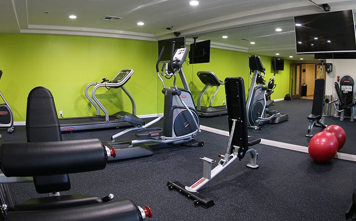 Fitness center with machines and mirrored wall at the Hollywood apartments community The Joshua