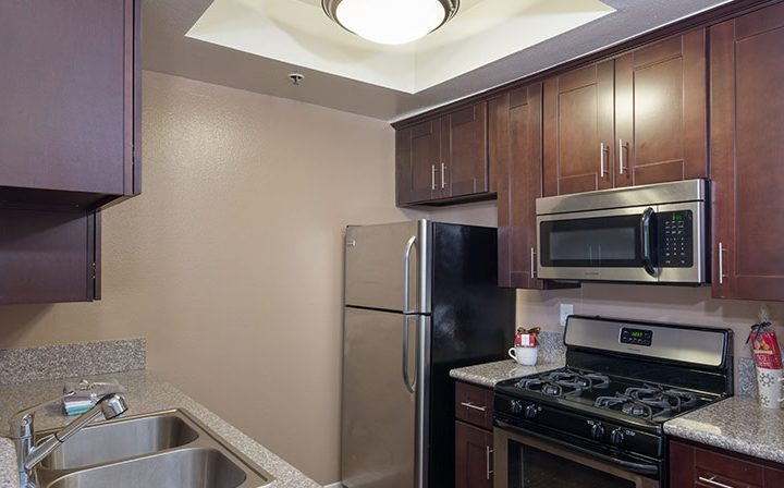 Kitchen with sink opposite range and brown cabinets at The Joshua, apartments in Hollywood