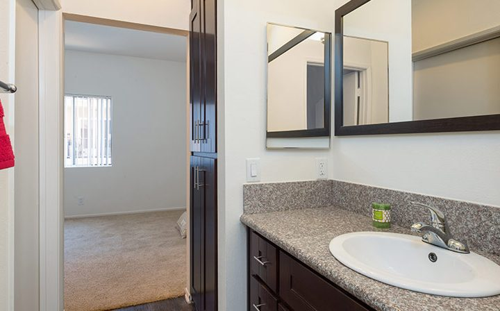Bathroom with brown cabinets next to bedroom at the Hollywood apartments community The Joshua
