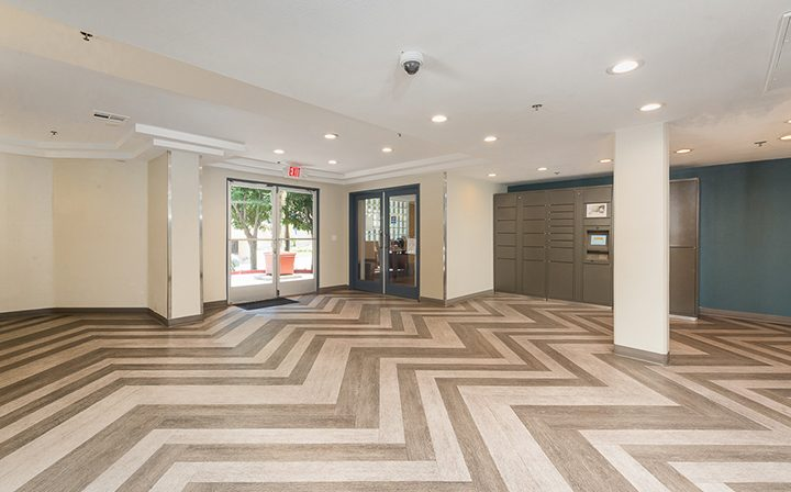 Lobby with zigzag floor pattern and package lockers at the Hollywood apartments community The Joshua