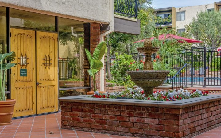 Brick fountain in brick courtyard next to ornate doors at The Palms, apartments in West Los Angeles