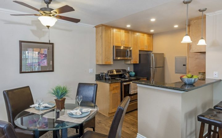 Furnished dining area with glass table next to kitchen at The Palms, West Los Angeles apartments