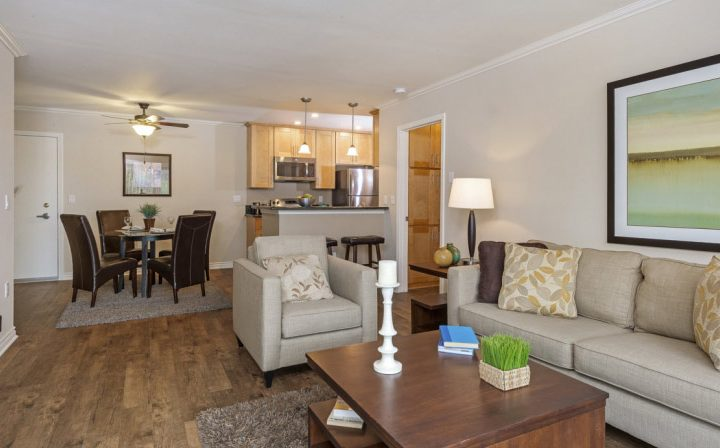 Furnished living room with wall art, TV, and more at The Palms, apartments in West Los Angeles