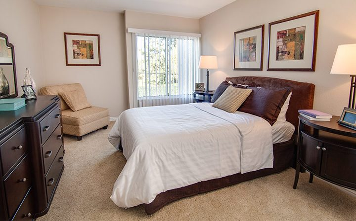 Carpeted, furnished bedroom with wall art and dresser at The Palms, West Los Angeles apartments
