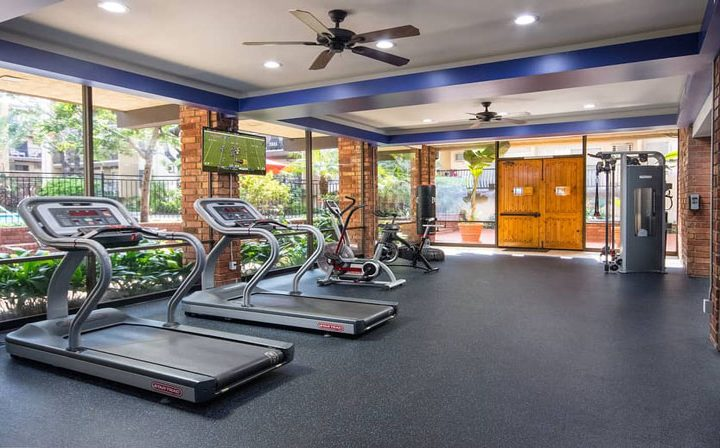 Sunny fitness center with treadmills by large windows at The Palms, West Los Angeles apartments