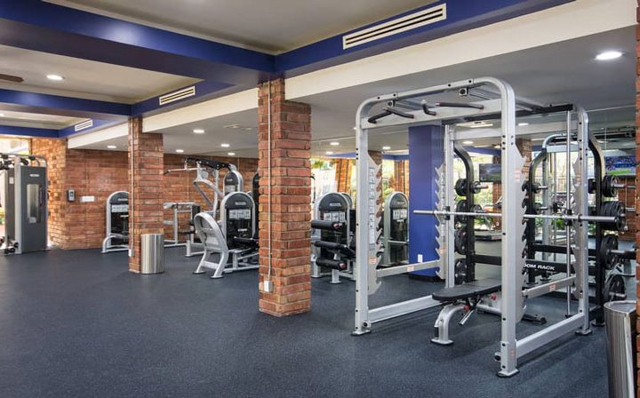 Weight racks in fitness center with blue ceiling at The Palms, apartments in West Los Angeles