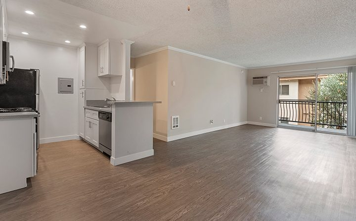 Unfurnished living room and kitchen with balcony exit at The Palms, West Los Angeles apartments