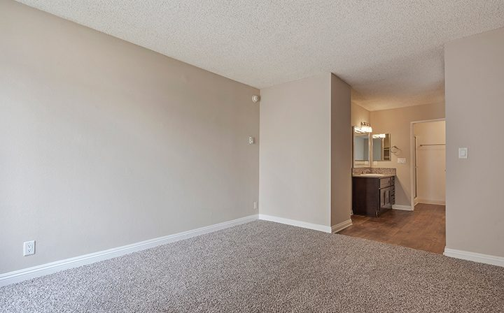 Carpeted, unfurnished bedroom next to bathroom at The Palms, apartments in West Los Angeles