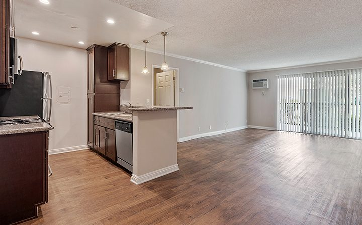 Unfurnished living room and kitchen with brown cabinets at The Palms, apartments in West Los Angeles