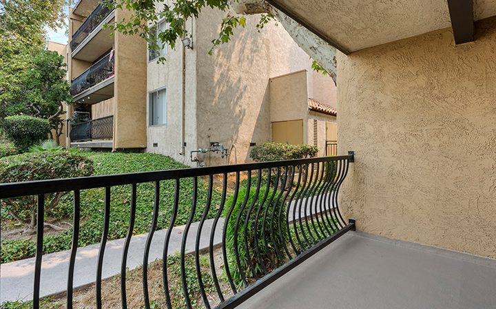 Balcony outside unit with curved black railing at The Palms, apartments in West Los Angeles