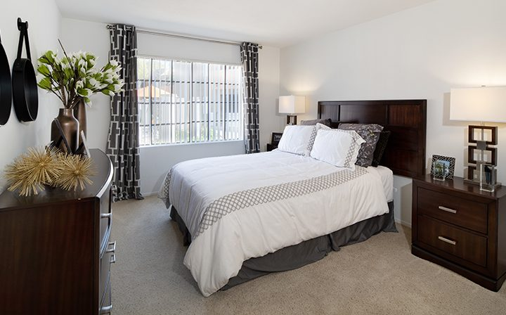 Carpeted, furnished bedroom with large window at The Ranch at Moorpark, Moorpark apartments