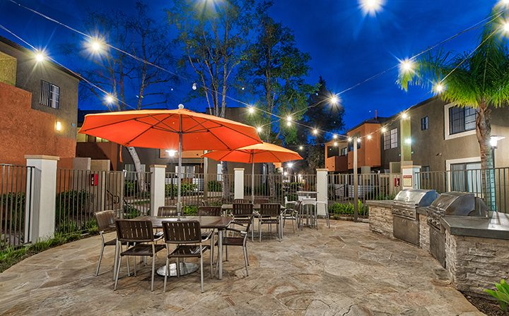 Chairs under orange umbrellas by BBQ grills at The Ranch at Moorpark, apartments in Moorpark
