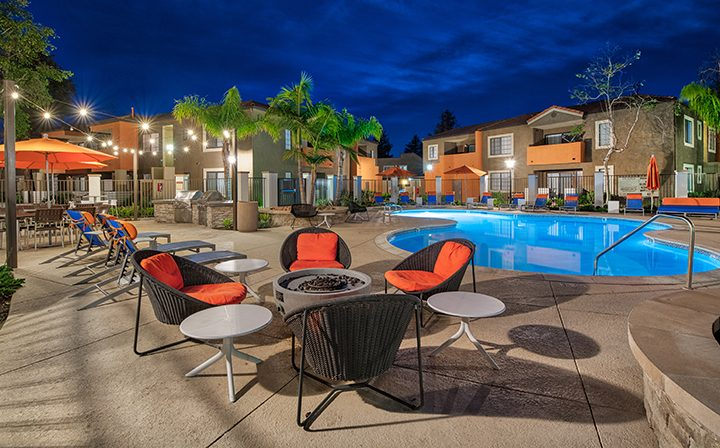 Orange chairs and umbrellas by large pool at night at The Ranch at Moorpark, Moorpark apartments