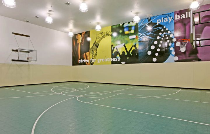 Indoor basketball court with colorful motivational posters at The Retreat at Bothell apartments