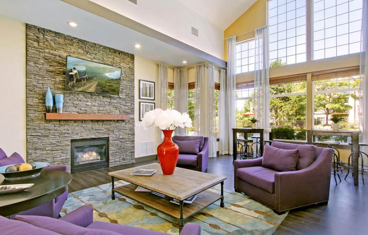 The Retreat at Bothell apartments clubhouse with large windows, big screen television, and fireplace
