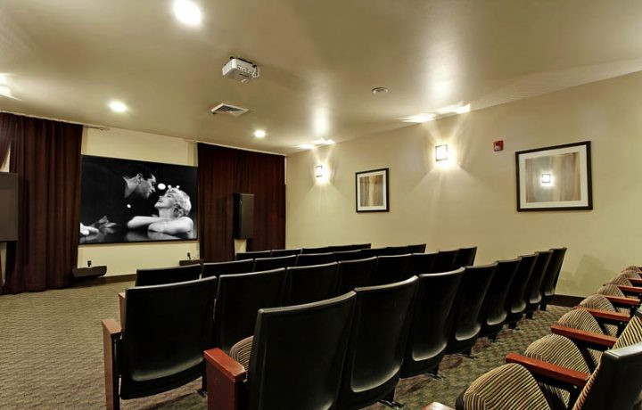 On-site theater with seating rows and movie curtain at Seattle area apartment The Retreat at Bothell