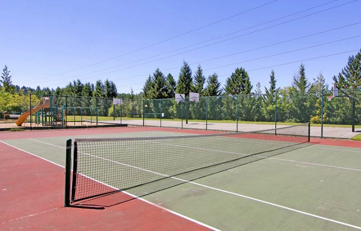 Outdoor tennis and basketball courts and children's playground at The Retreat at Bothell apartments