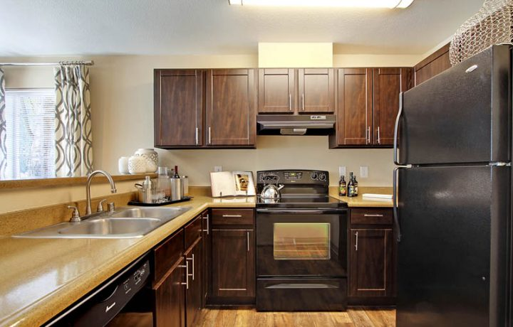 The Retreat at Bothell apartments kitchen interior with range, dishwasher, refrigerator and cabinets