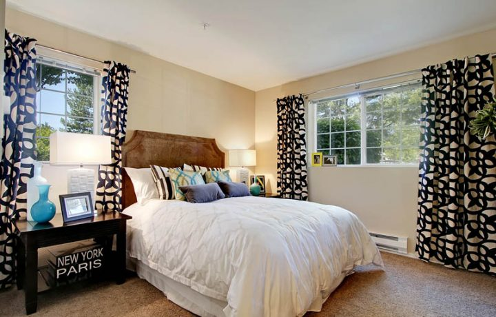 Furnished bedroom interior with view of trees at Seattle area apartment The Retreat at Bothell