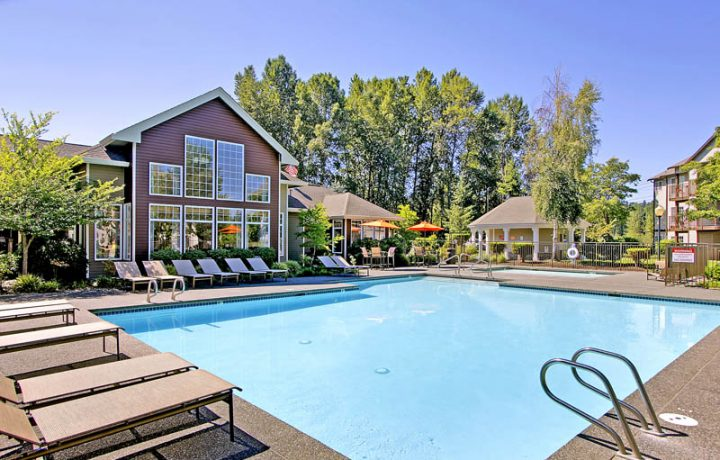 Large outdoor pool and spa with reclining chairs at Seattle area apartments The Retreat at Bothell
