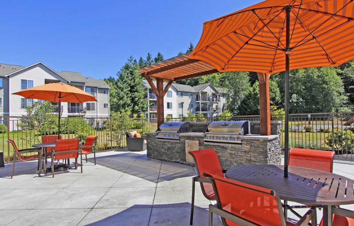 Two BBQ grills and umbrella shaded outdoor seating at Seattle area apartments The Retreat at Bothell