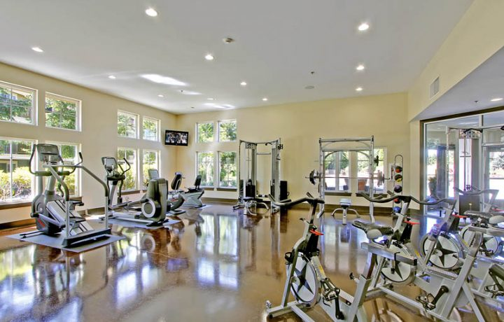 The Retreat at Bothell apartments fitness room with large windows, treadmills, and bike machines